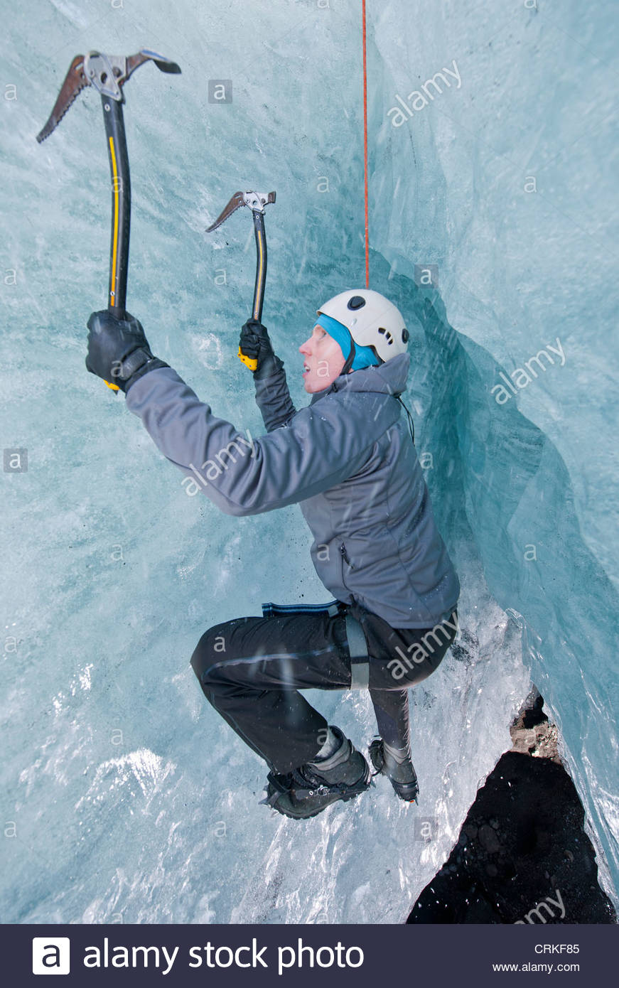 Climber climbing out of ice cave - Stock Image