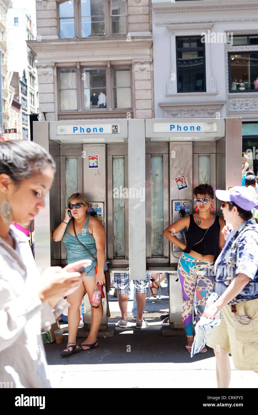 girls in pay phone box, New York - Stock Image