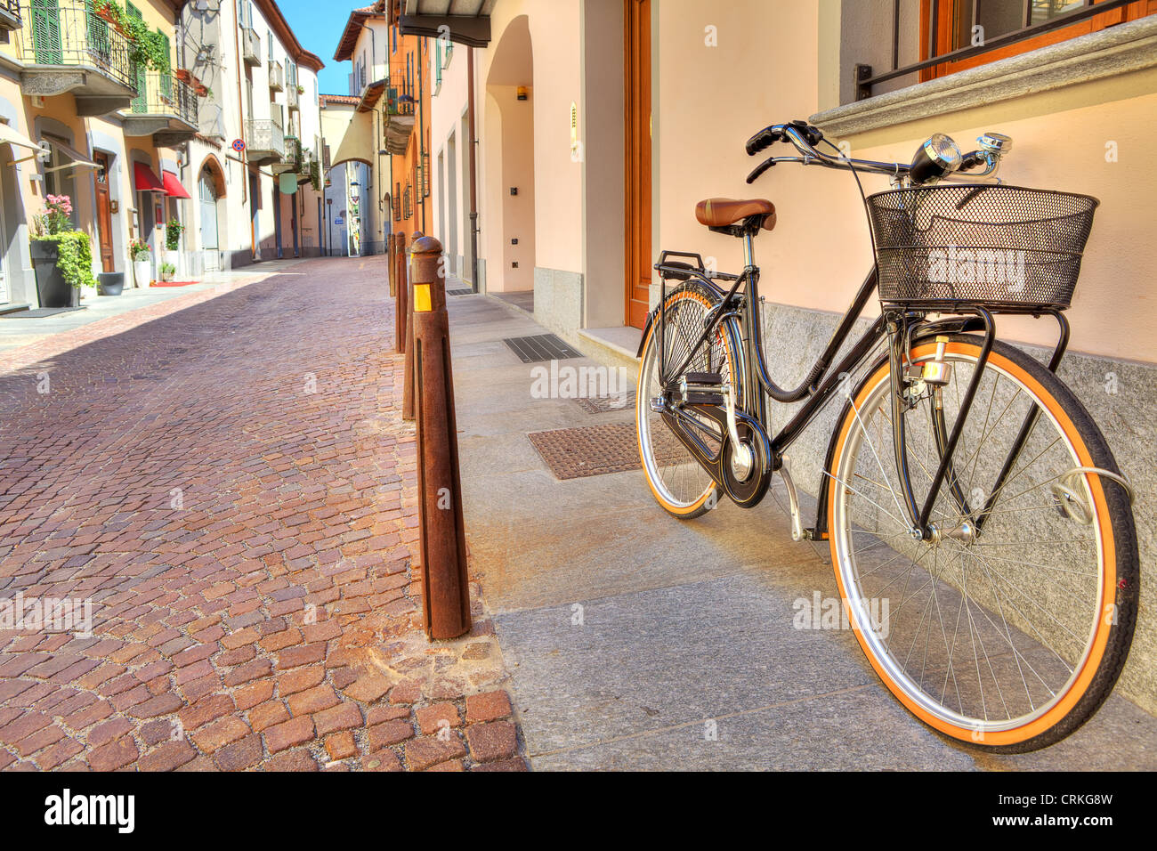 City bicycle on the cobbled street of Alba in Piedmont, Northern Italy. - Stock Image