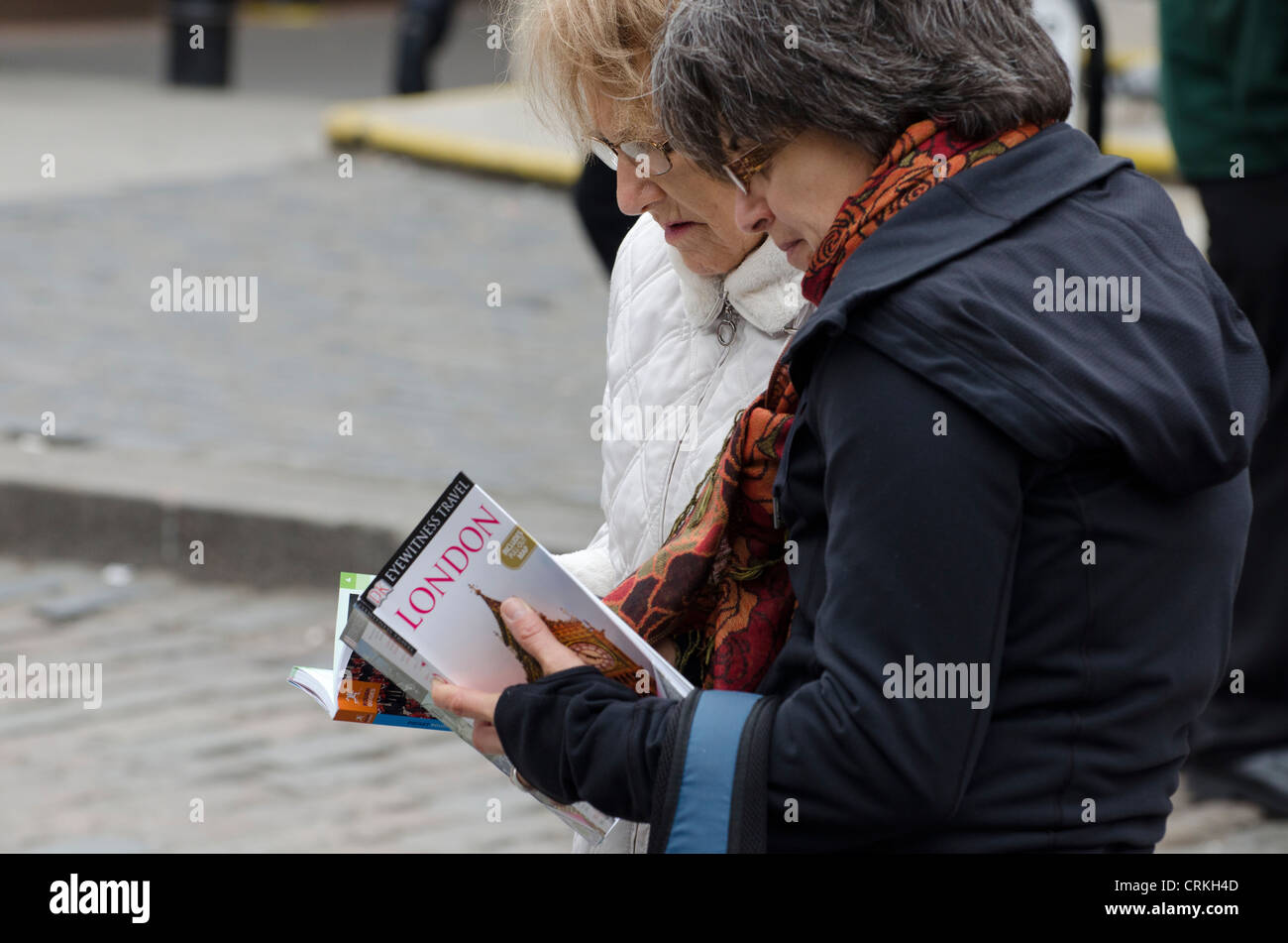Two middle aged women tourists search London guide books in street Covent garden London Uk - Stock Image