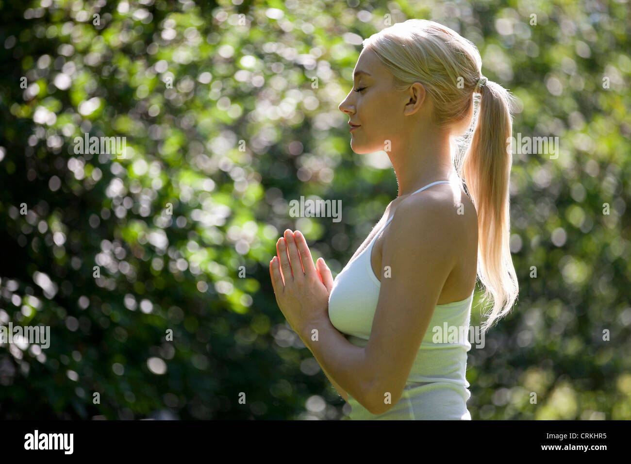 A young woman practicing yoga outside, hands in prayer position Stock Photo