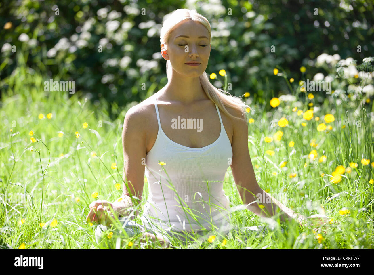 A young woman meditating outside, eyes closed - Stock Image