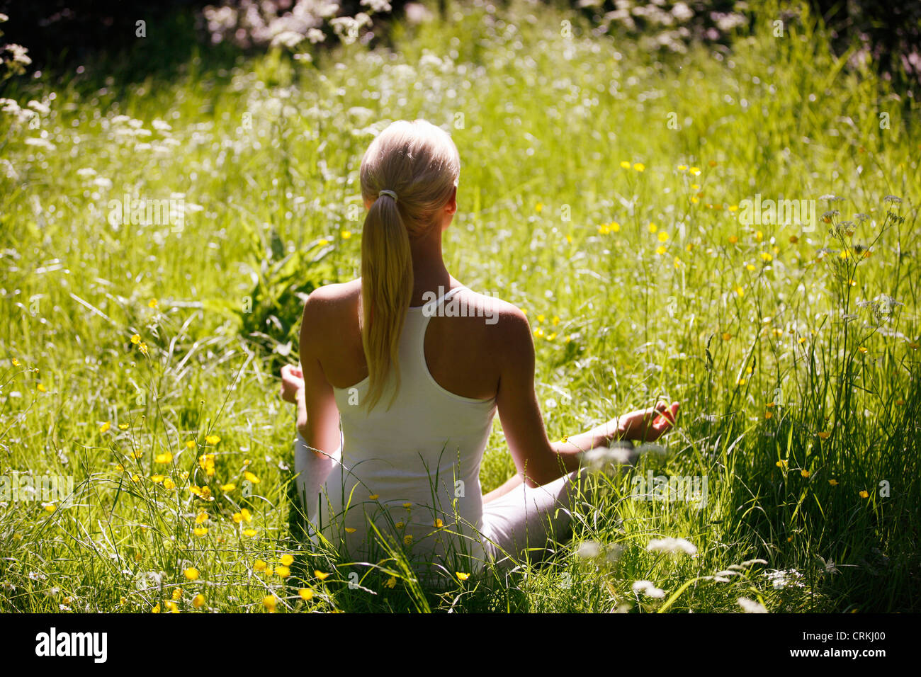 A young woman meditating outside, back view - Stock Image