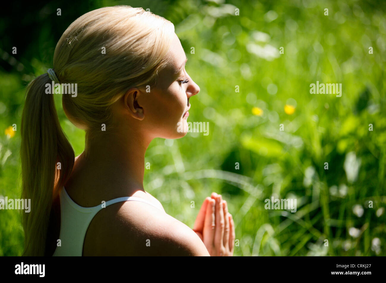 A young woman practicing yoga outside, hands in prayer position - Stock Image