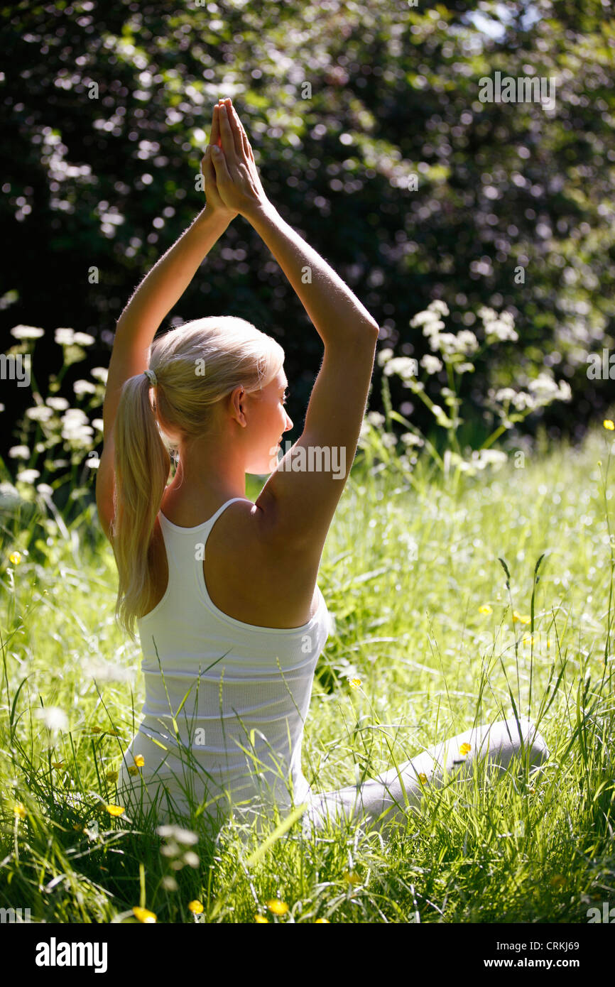 A young woman practicing yoga outside Stock Photo