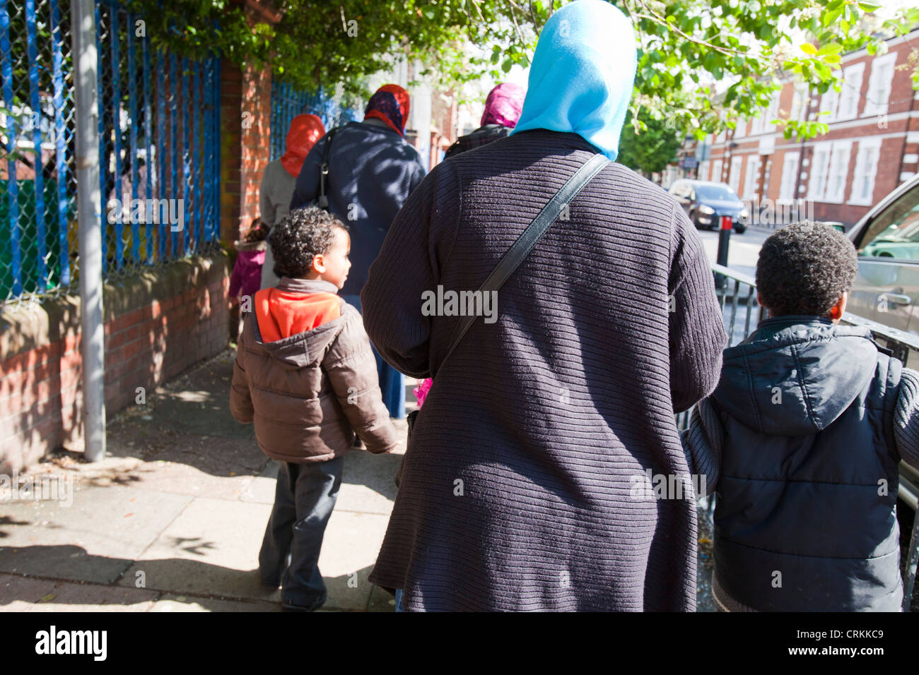 Muslim mothers picking their children up from infant school in Queens Park, London, UK. - Stock Image