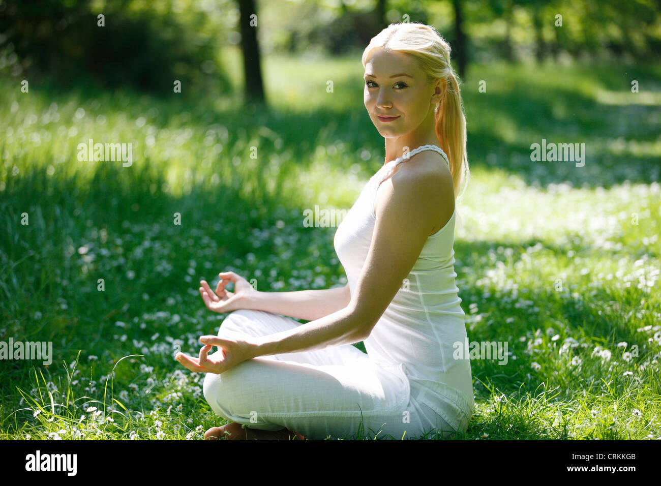 A young woman practicing yoga outside, looking to camera - Stock Image