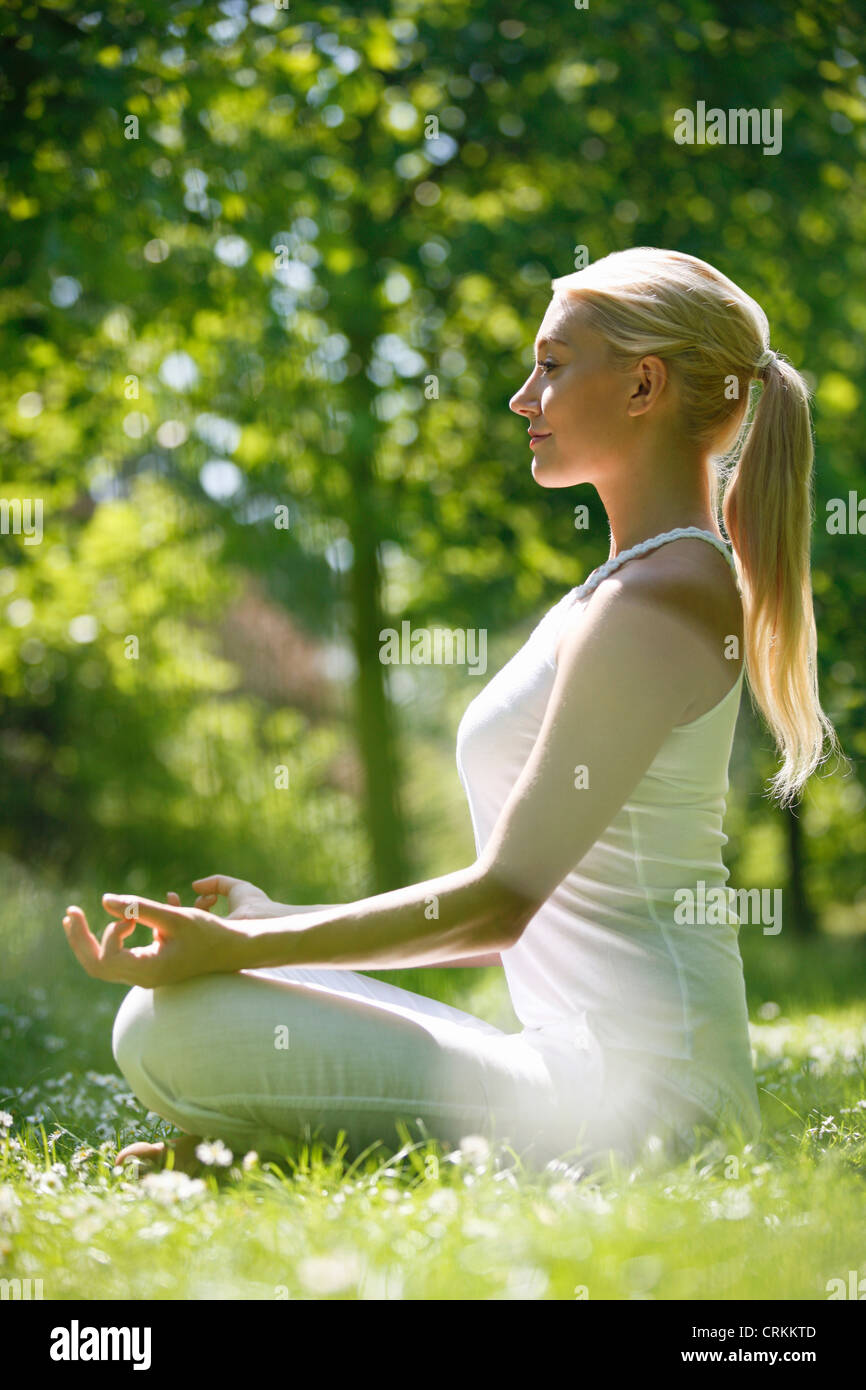 A young woman meditating outside - Stock Image