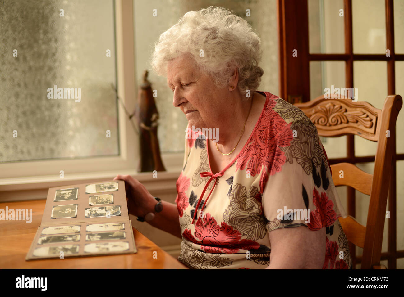 An elderly lady looking at photographs in an album sat at table - Stock Image