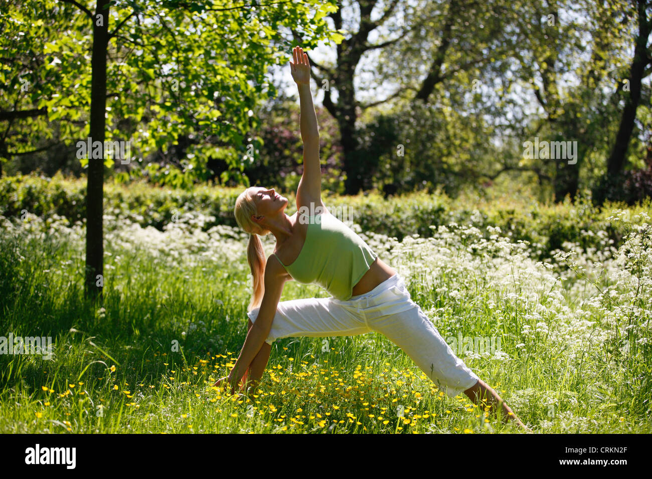 A young woman practicing yoga outside, triangle pose - Stock Image