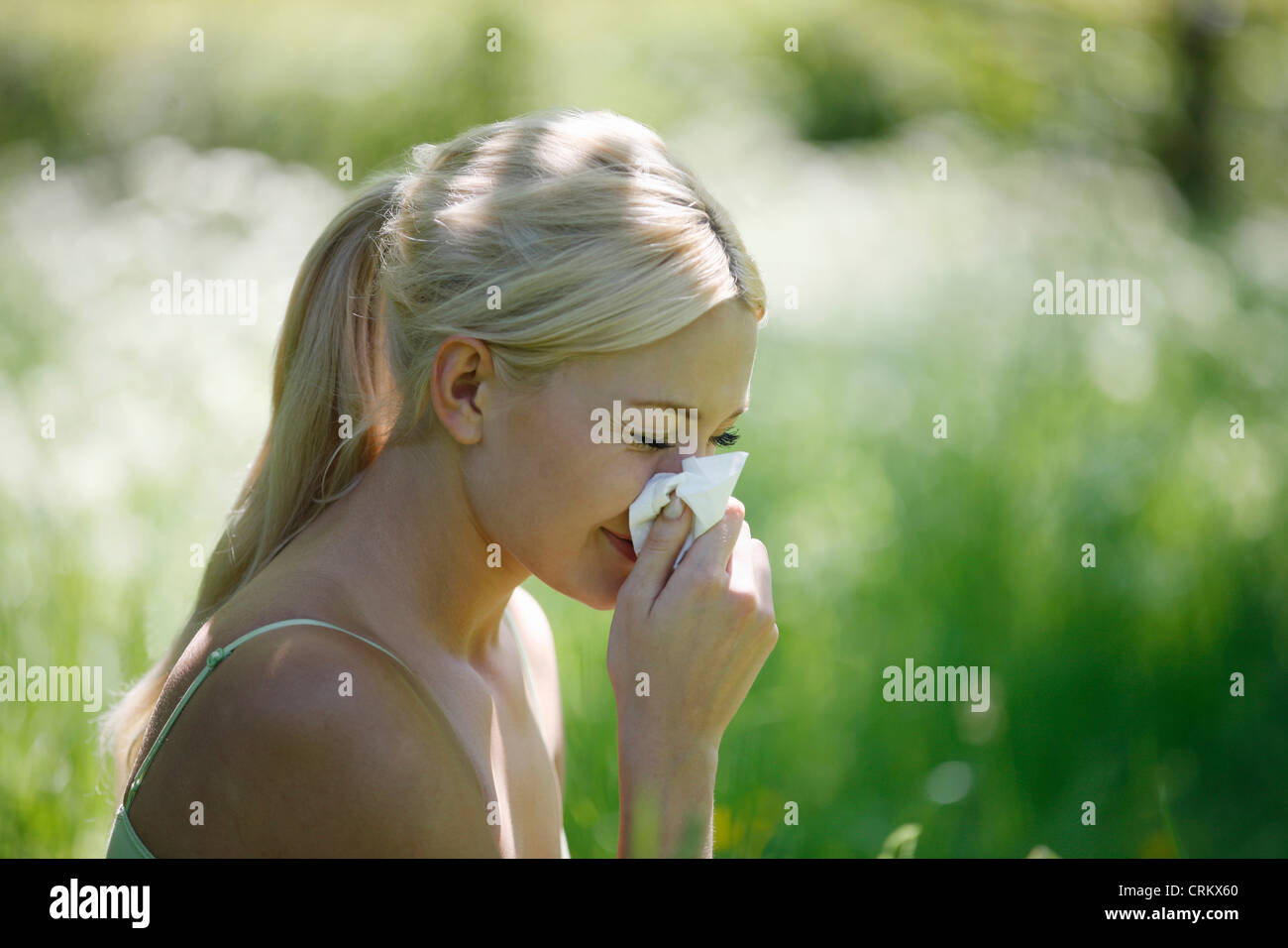 A young blonde woman sneezing into a tissue - Stock Image