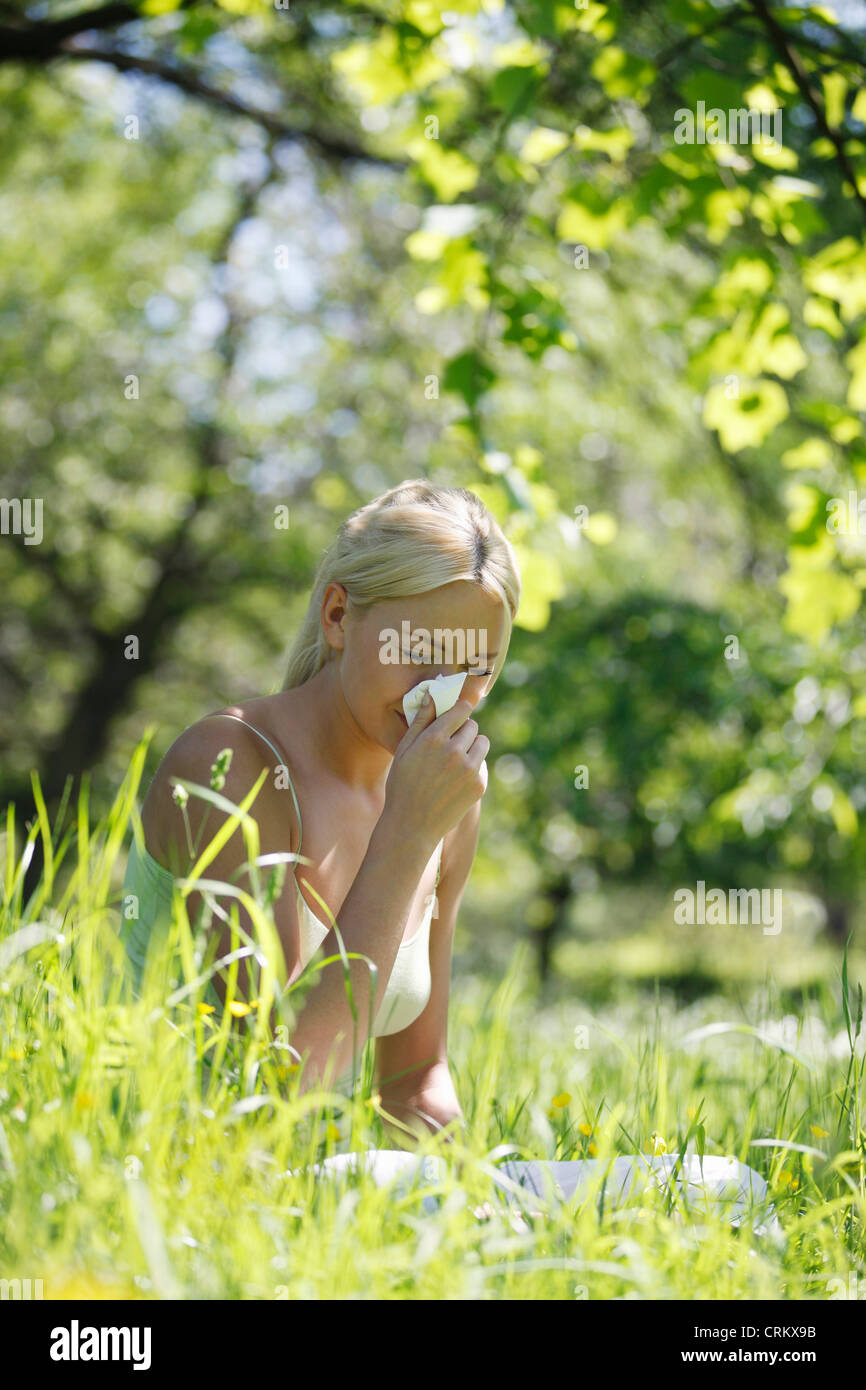 A young blond woman sneezing into a tissue - Stock Image