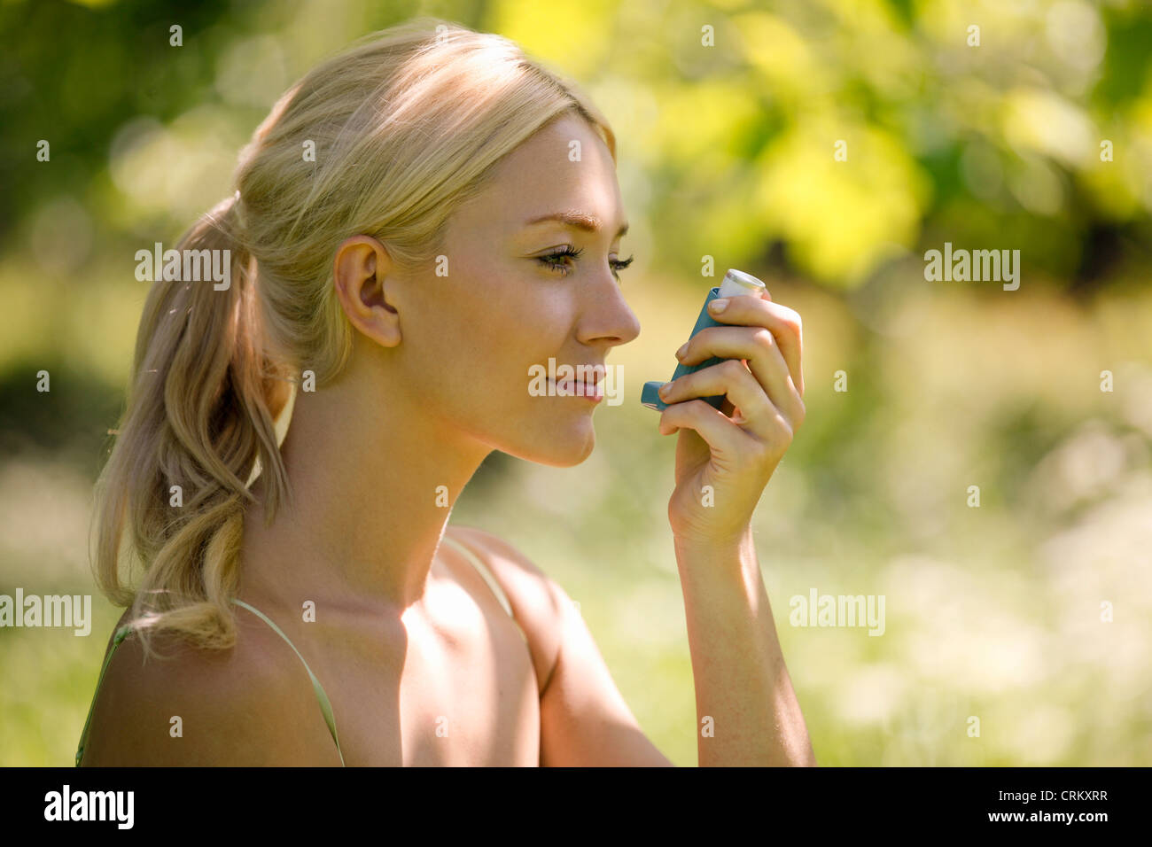 A young blond woman sitting in the grass using a asthma inhaler - Stock Image