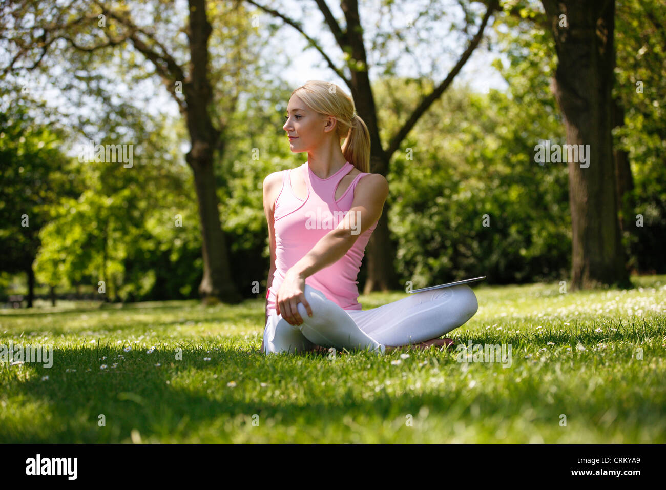 A young blond woman sitting in the grass, stretching - Stock Image