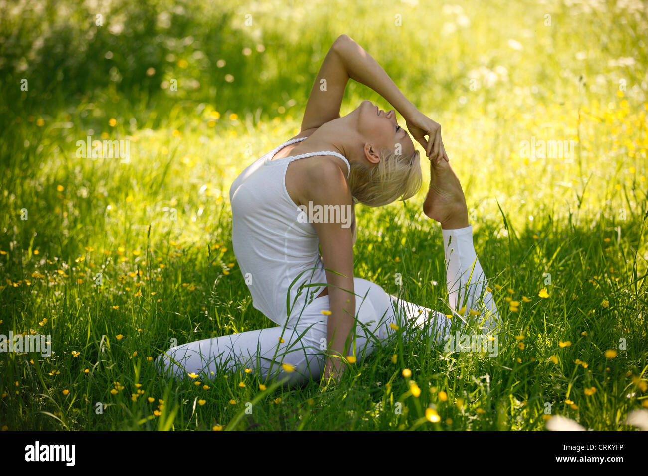 A young woman practicing yoga outside, pigeon pose - Stock Image