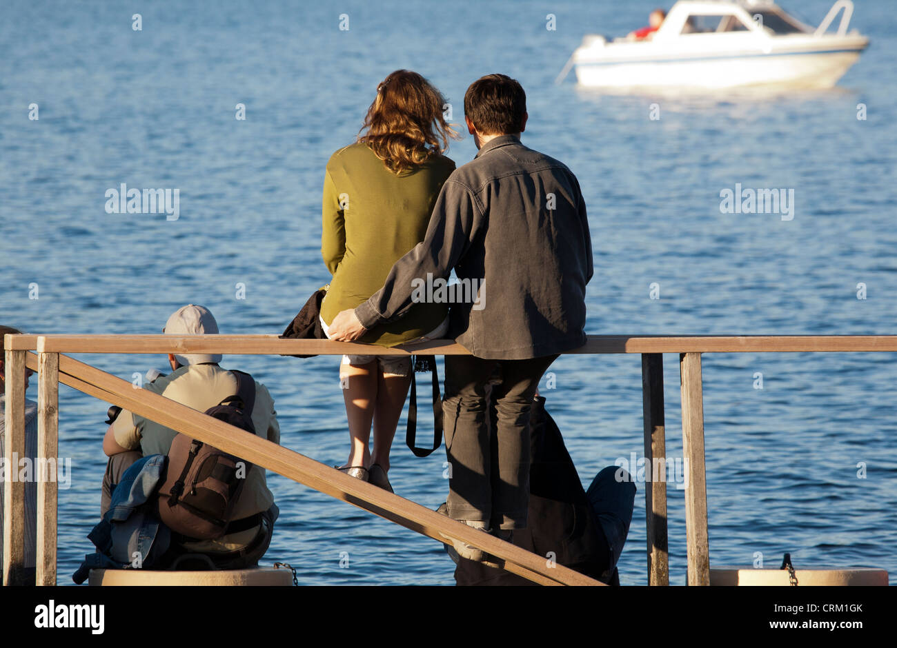 Man and woman sitting on handrail at harbour, Finland - Stock Image
