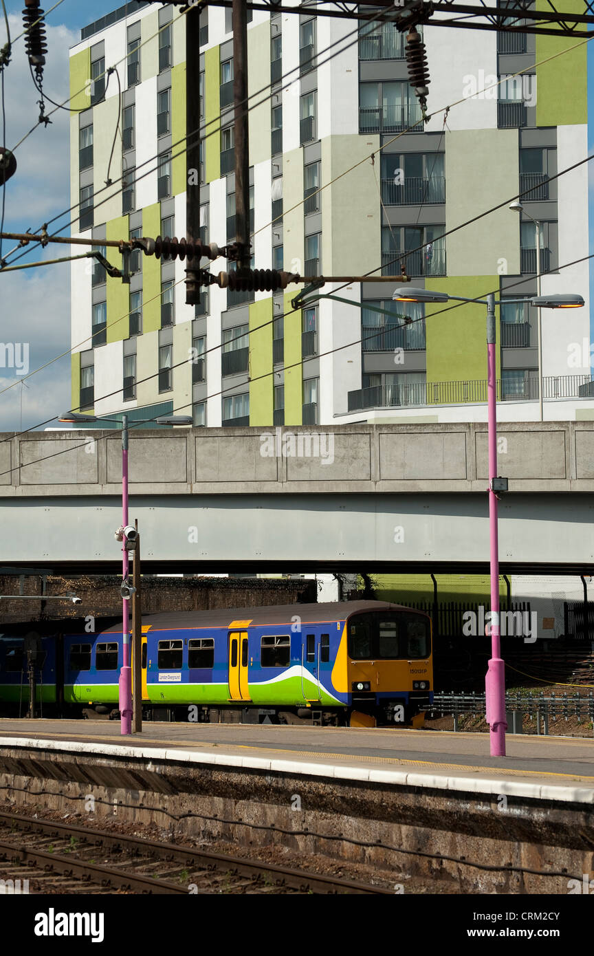 Passenger train in London Overground livery waiting at a railway station in England. - Stock Image