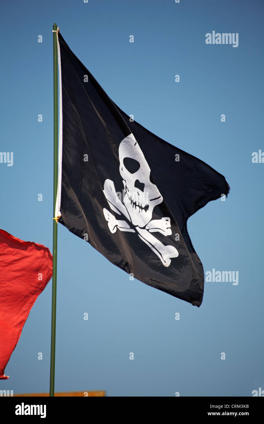 Jolly Roger pirate flag blowing in the wind at Poole - Stock Image