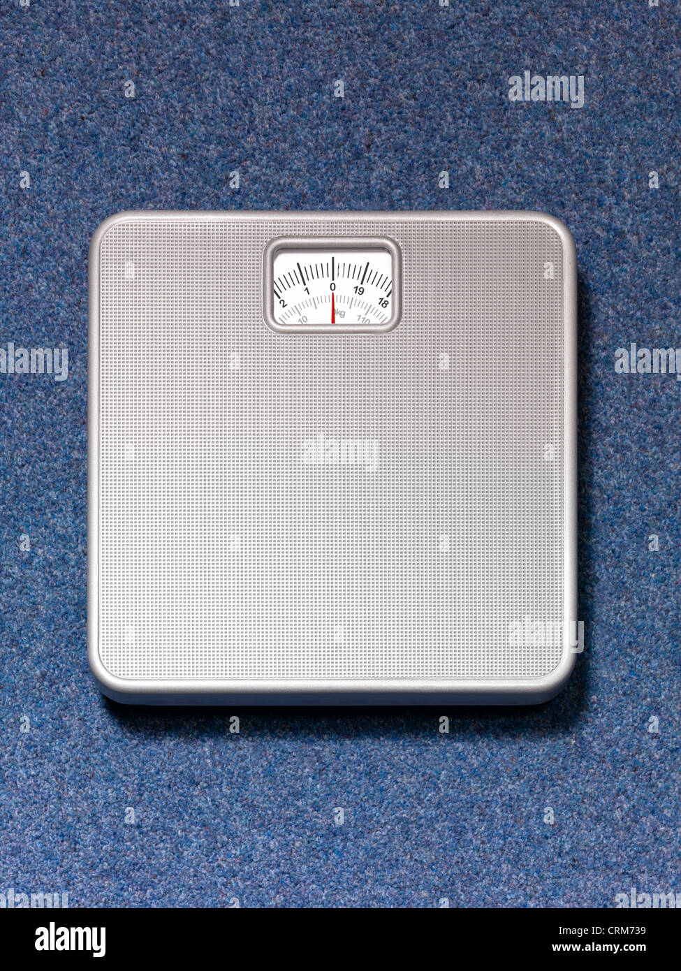 Silver weighing scales on a blue carpet background Stock Photo