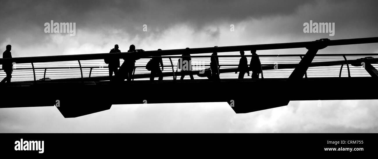 Silhouette of people Crossing Millennium Bridge - Stock Image