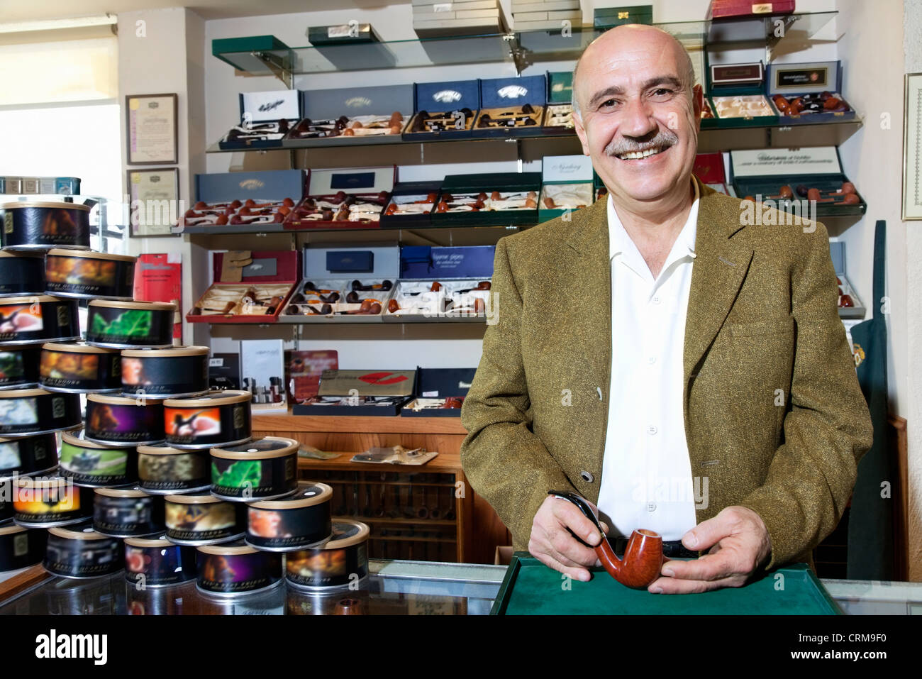 Portrait of a happy mature tobacco shop owner with cans on display - Stock Image