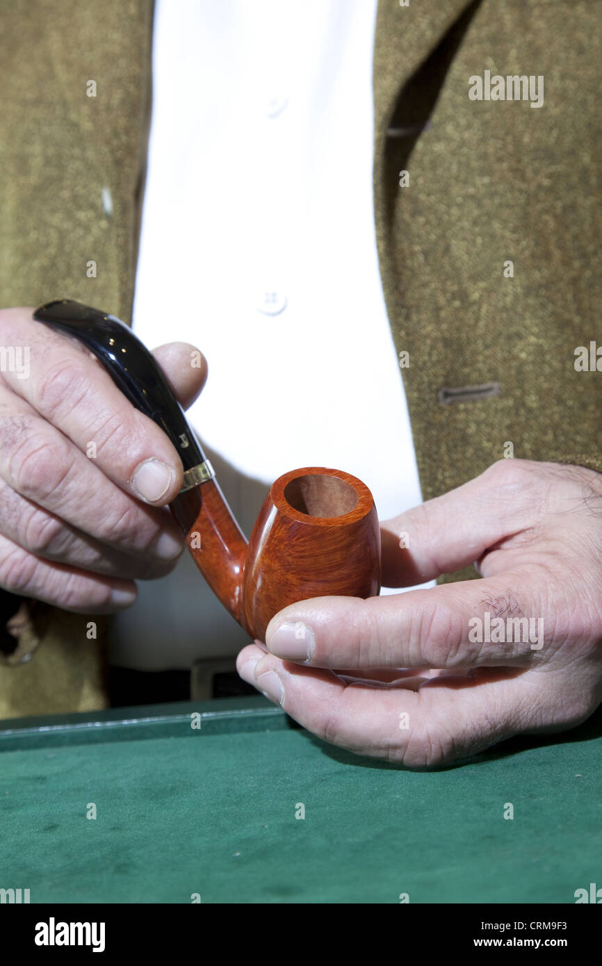 Close-up view of owner holding tobacco pipe - Stock Image