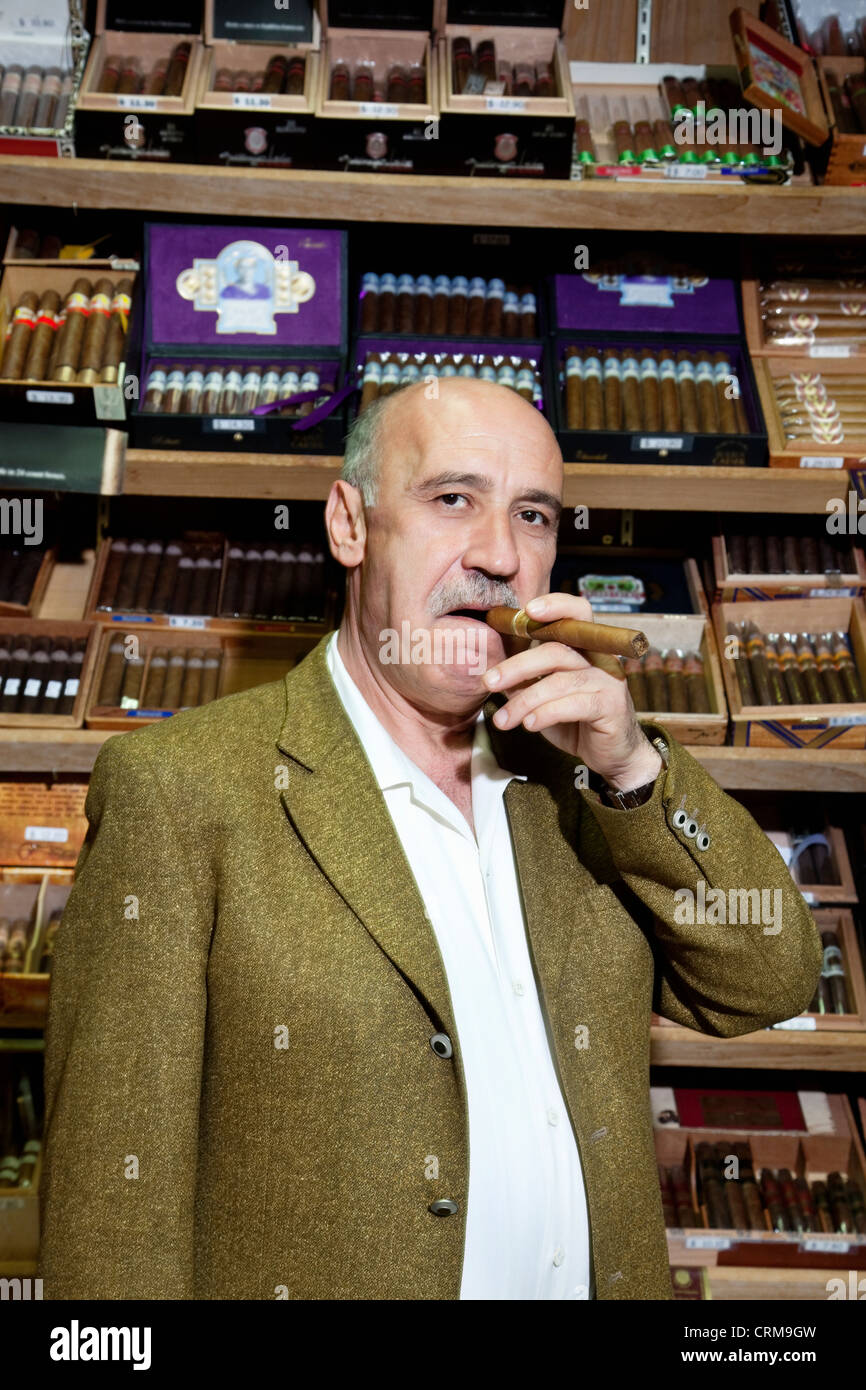 Portrait of a mature man smoking cigar in tobacco store - Stock Image