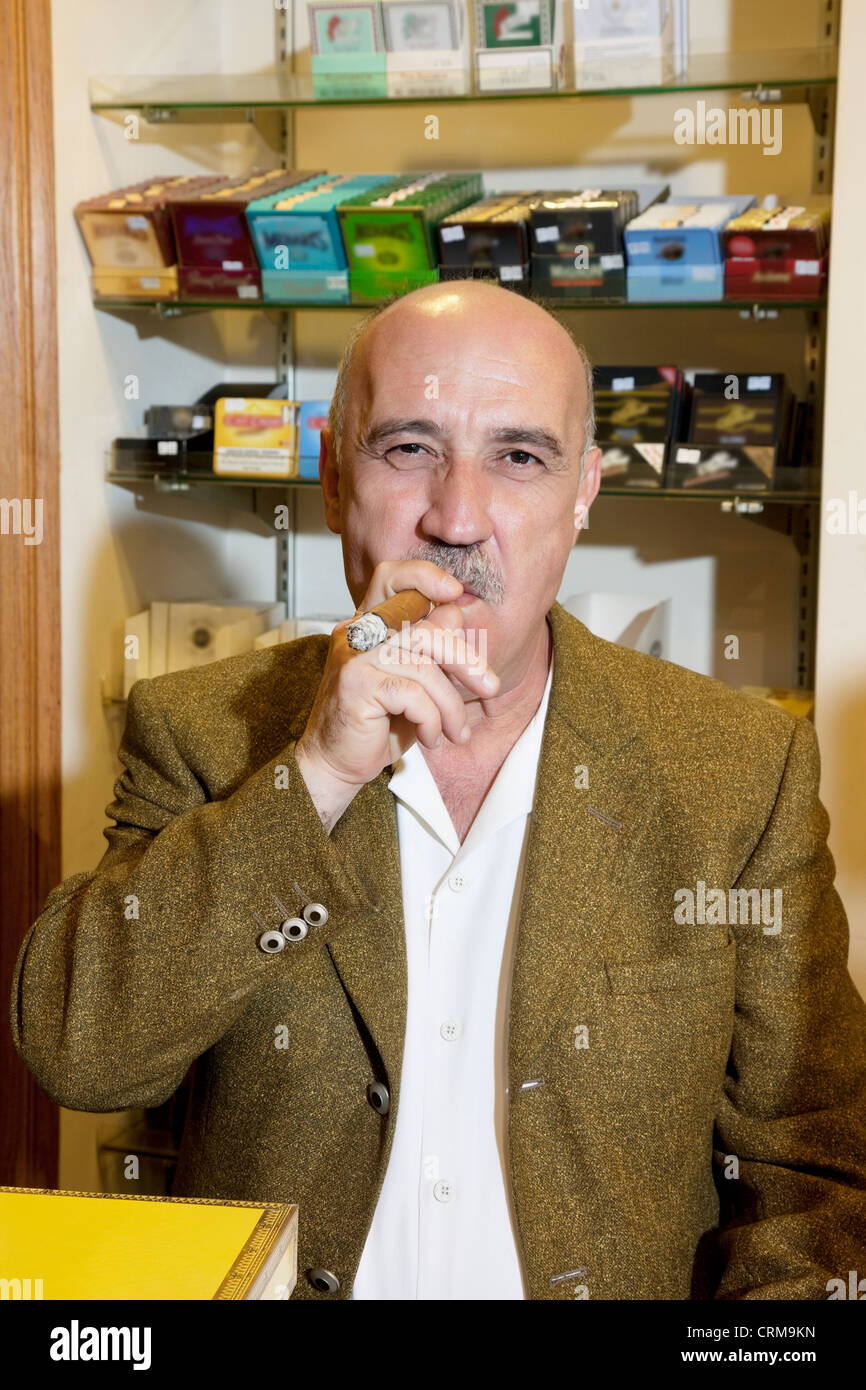 Portrait of mature tobacco store owner smoking cigar - Stock Image