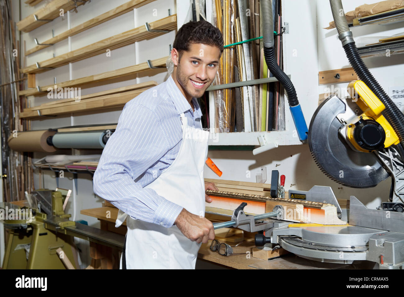 Portrait of a happy young craftsman standing by circular saw machinery - Stock Image