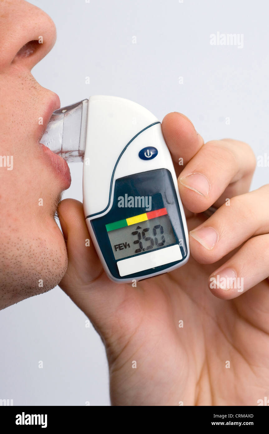 young male using his asthma inhaler - Stock Image
