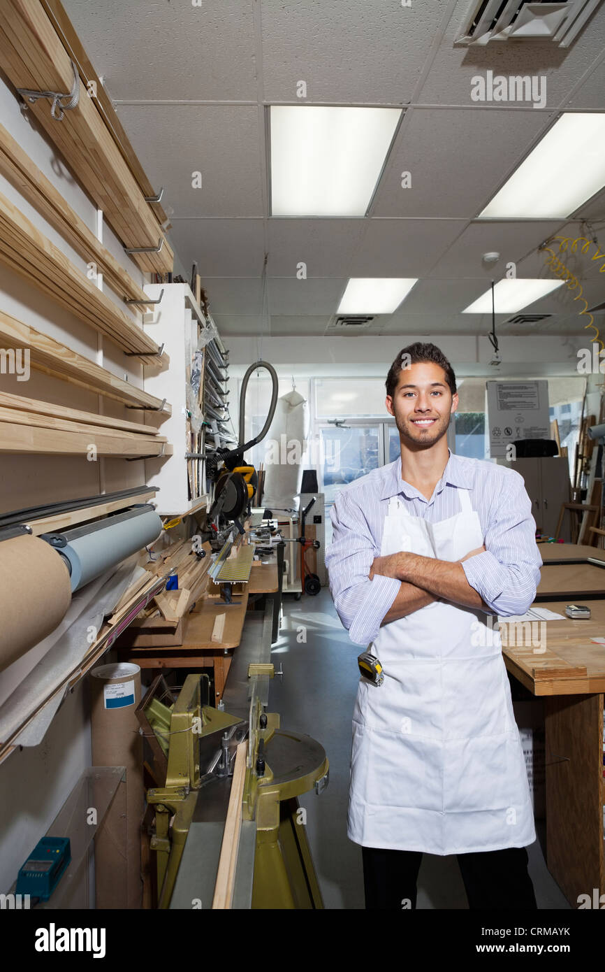Portrait of a happy skilled worker standing with arms crossed in workshop - Stock Image