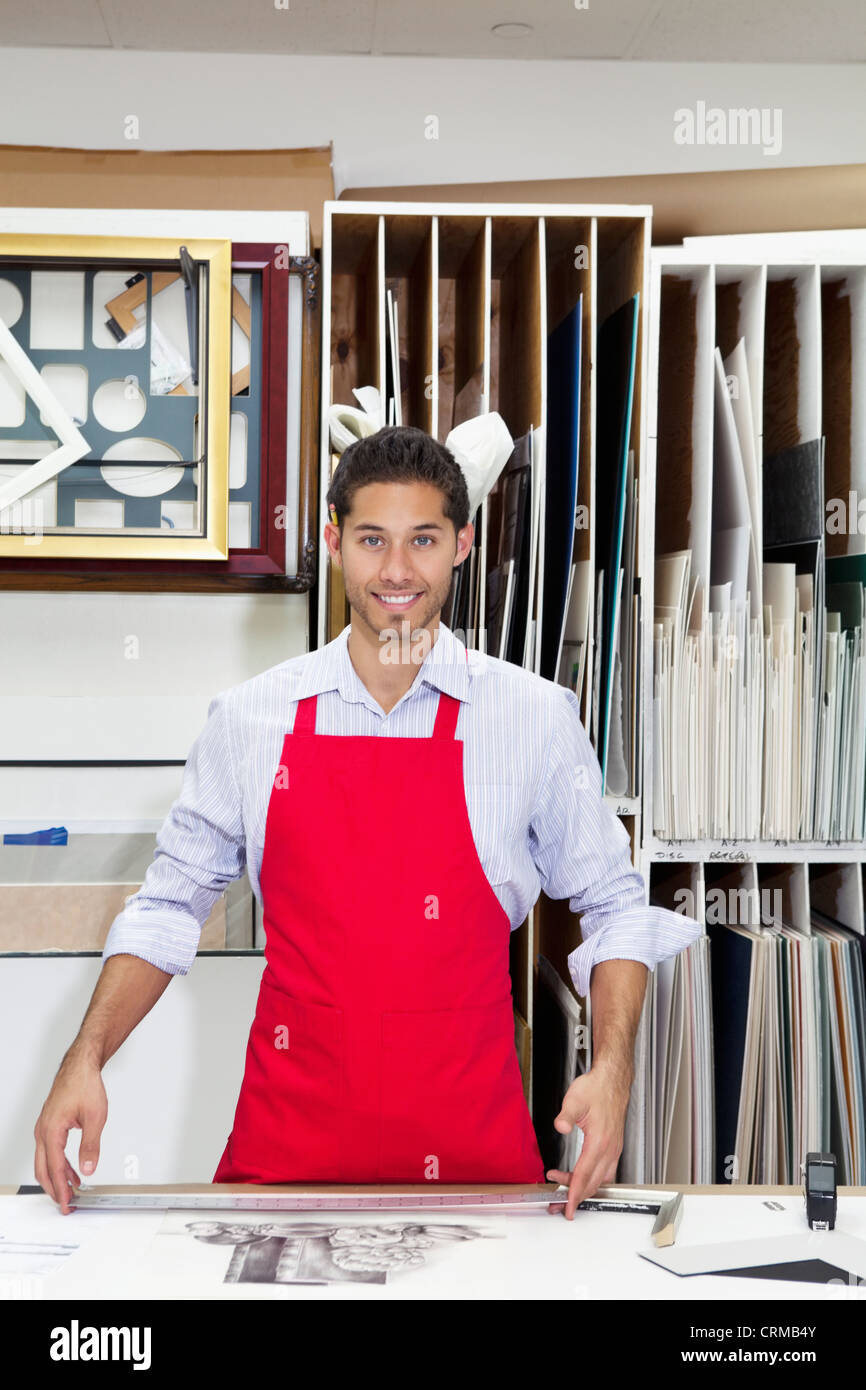 Portrait of a happy young skilled worker standing with meter stick in workshop - Stock Image