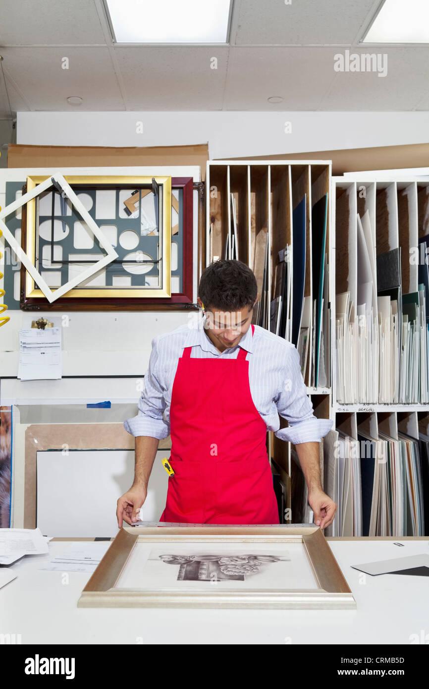 Young skilled worker adjusting frame on photograph - Stock Image