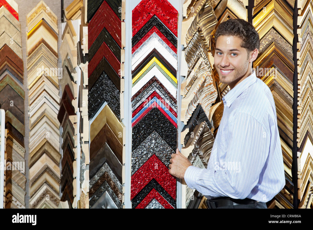 Portrait of a happy young man with multi colored frames in background - Stock Image