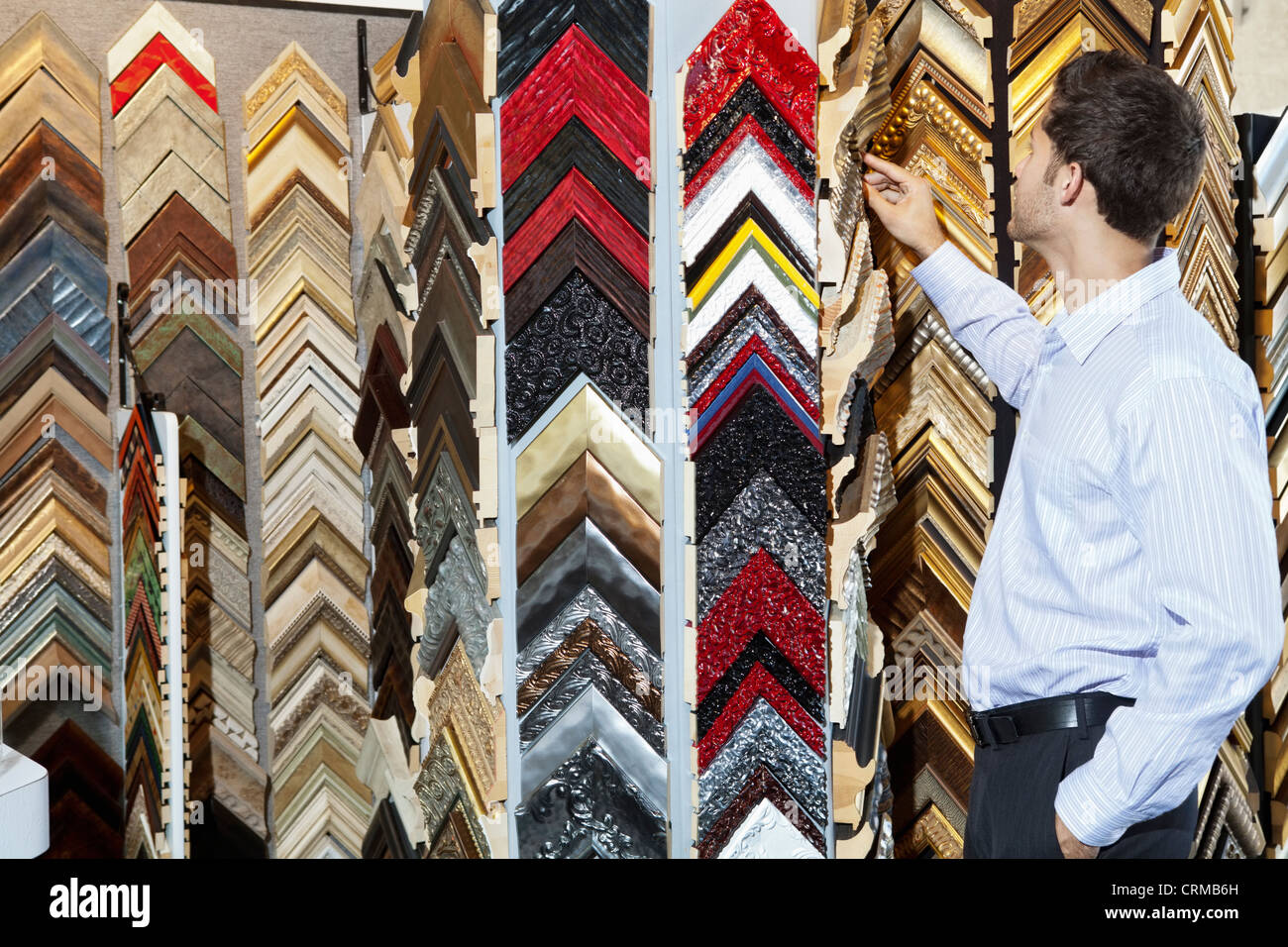 Young man looking at multi colored frames in store - Stock Image