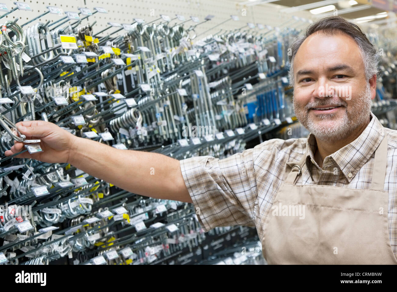Portrait of a happy mature salesperson holding metallic equipment in hardware store - Stock Image