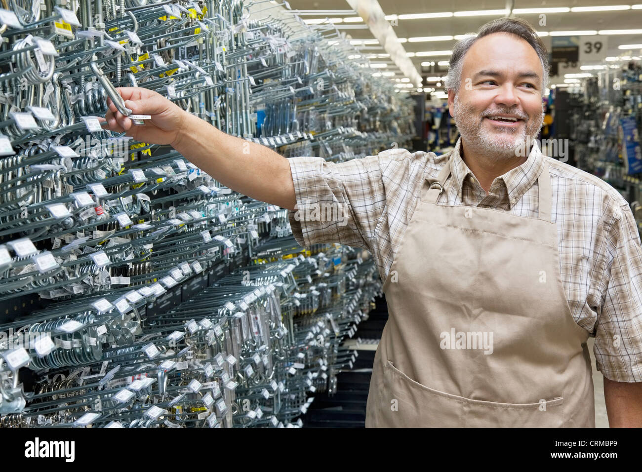 Happy mature salesperson holding metallic equipment while looking away in hardware store - Stock Image