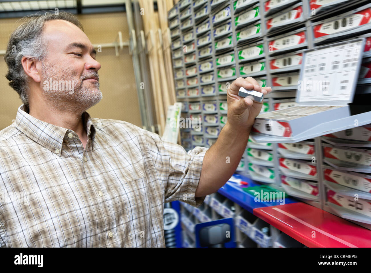 Happy mature man looking at staple pack in store - Stock Image