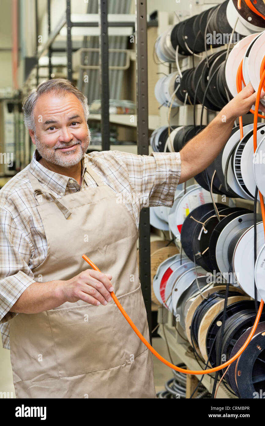 Portrait of a happy mature store clerk with electrical wire spool in hardware shop - Stock Image