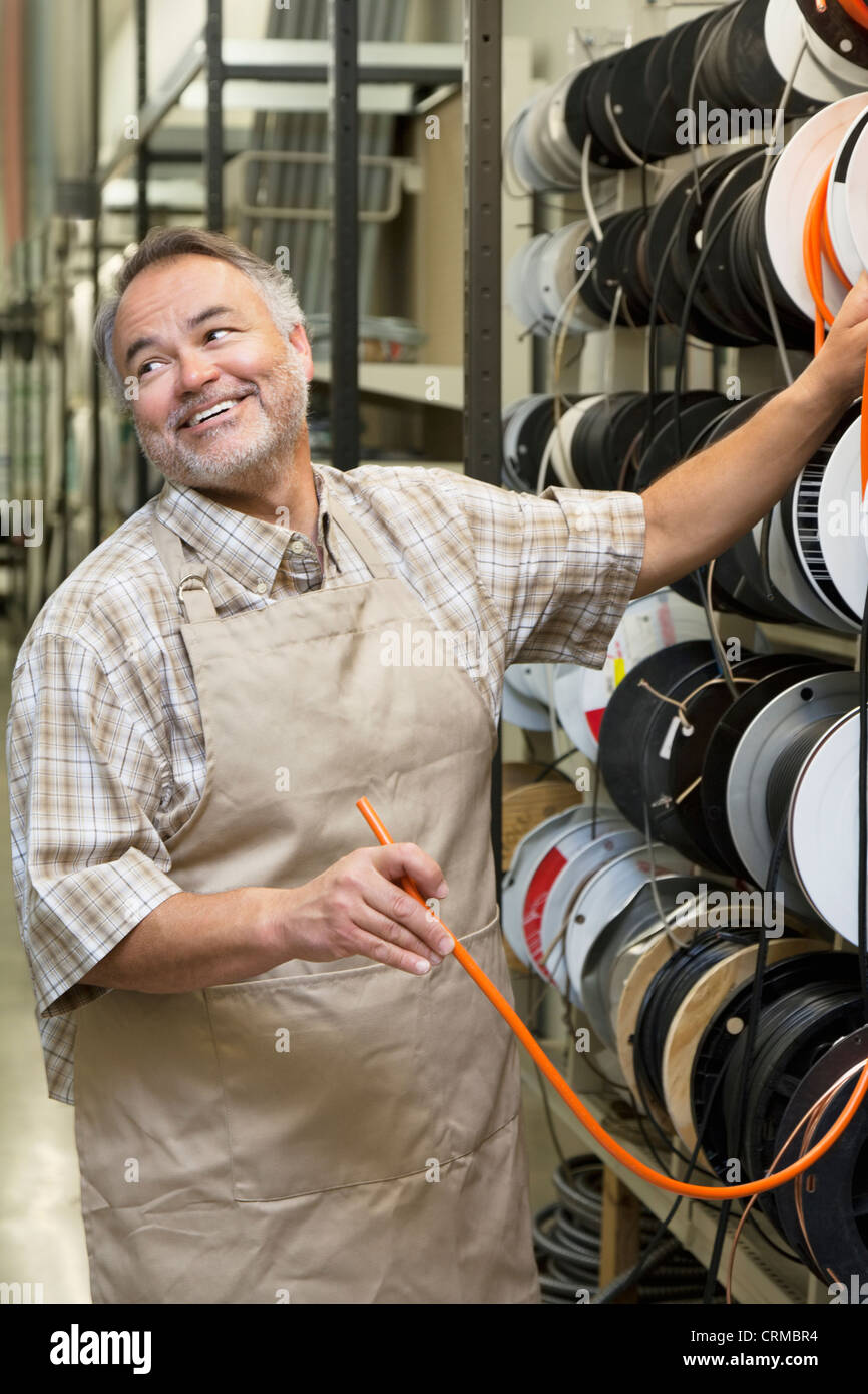 Happy mature salesperson standing by electrical wire spool while looking away in hardware store - Stock Image