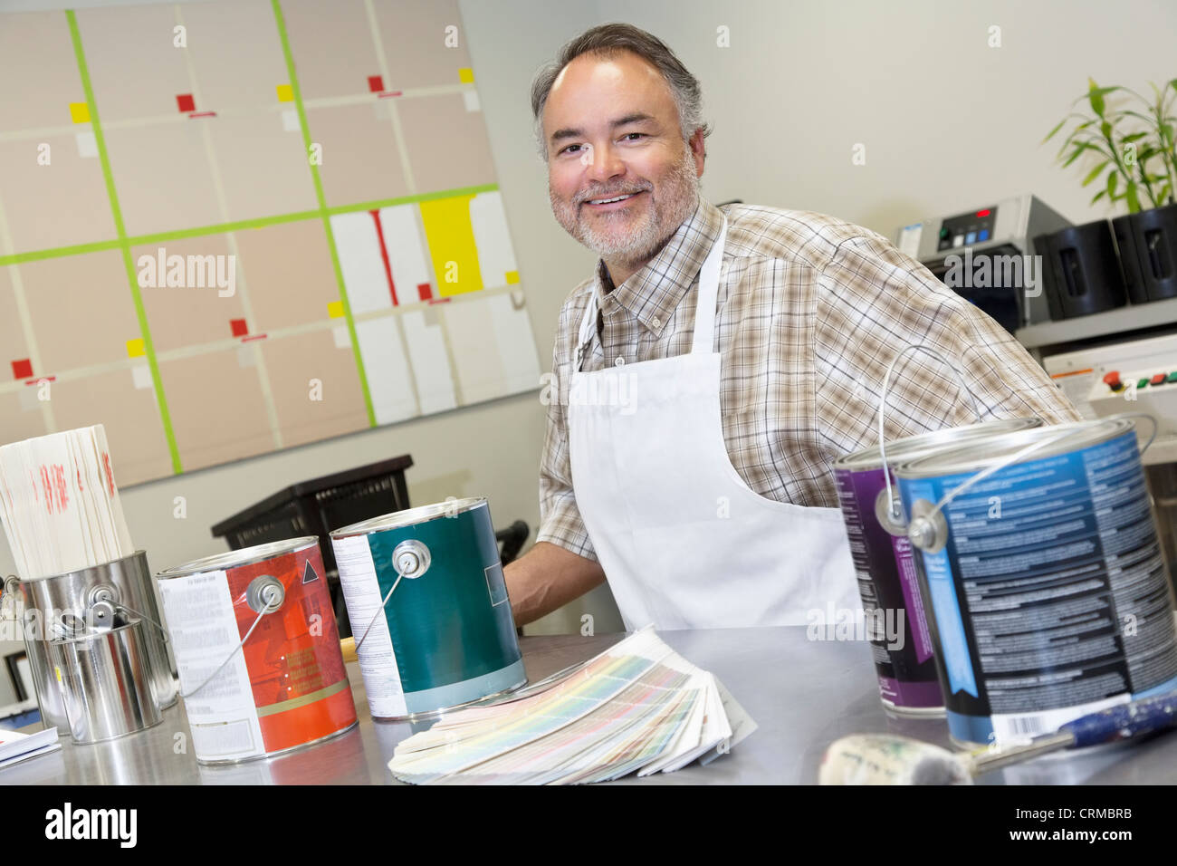 Portrait of a happy mature sales clerk at counter with paint cans in hardware store - Stock Image