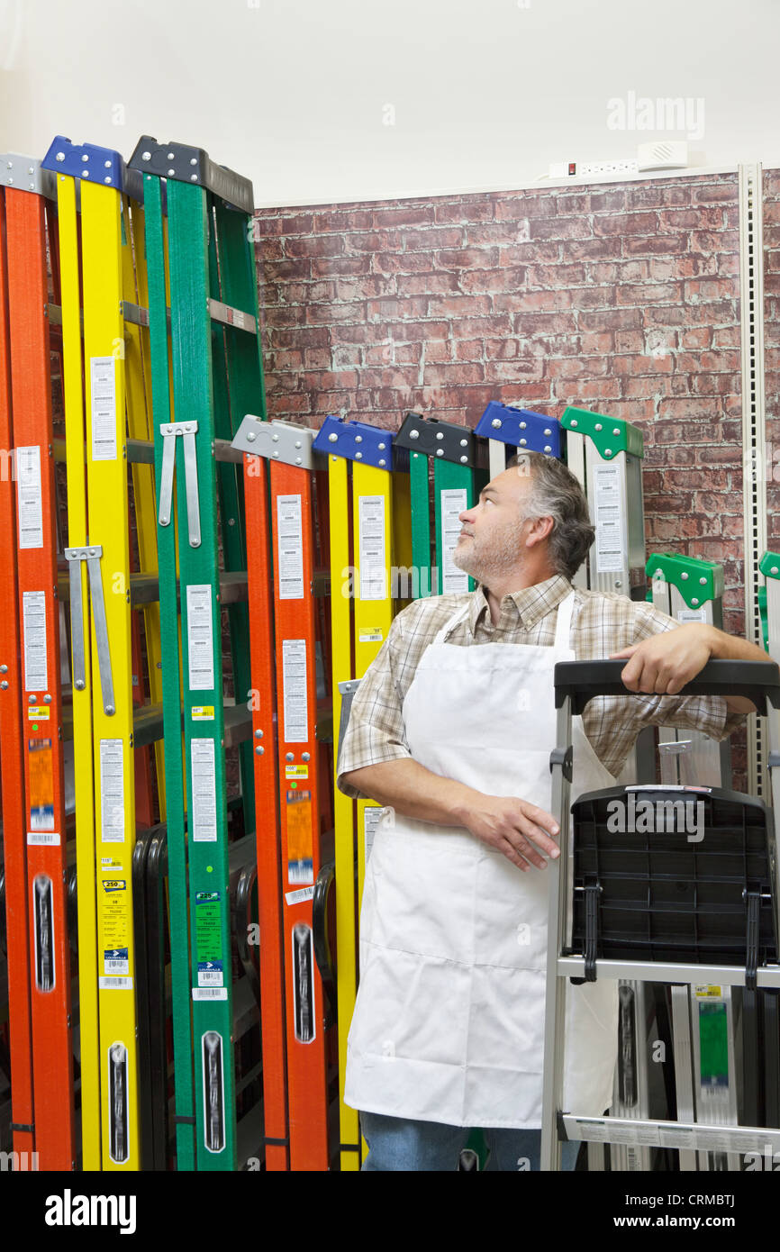 Mature salesperson standing by multicolored ladders in hardware store - Stock Image