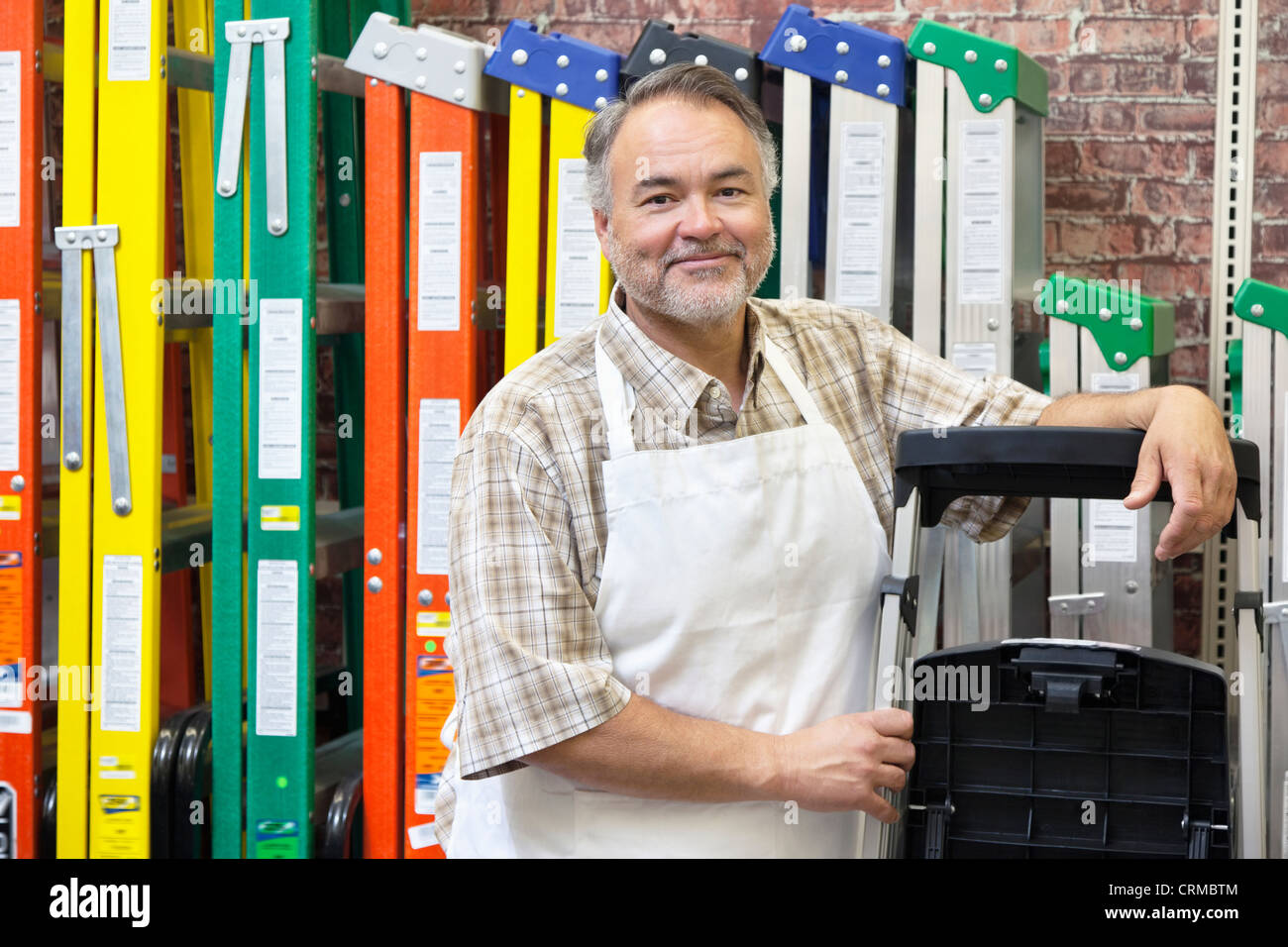 Portrait of happy mature store clerk standing by multicolored ladders in hardware shop - Stock Image