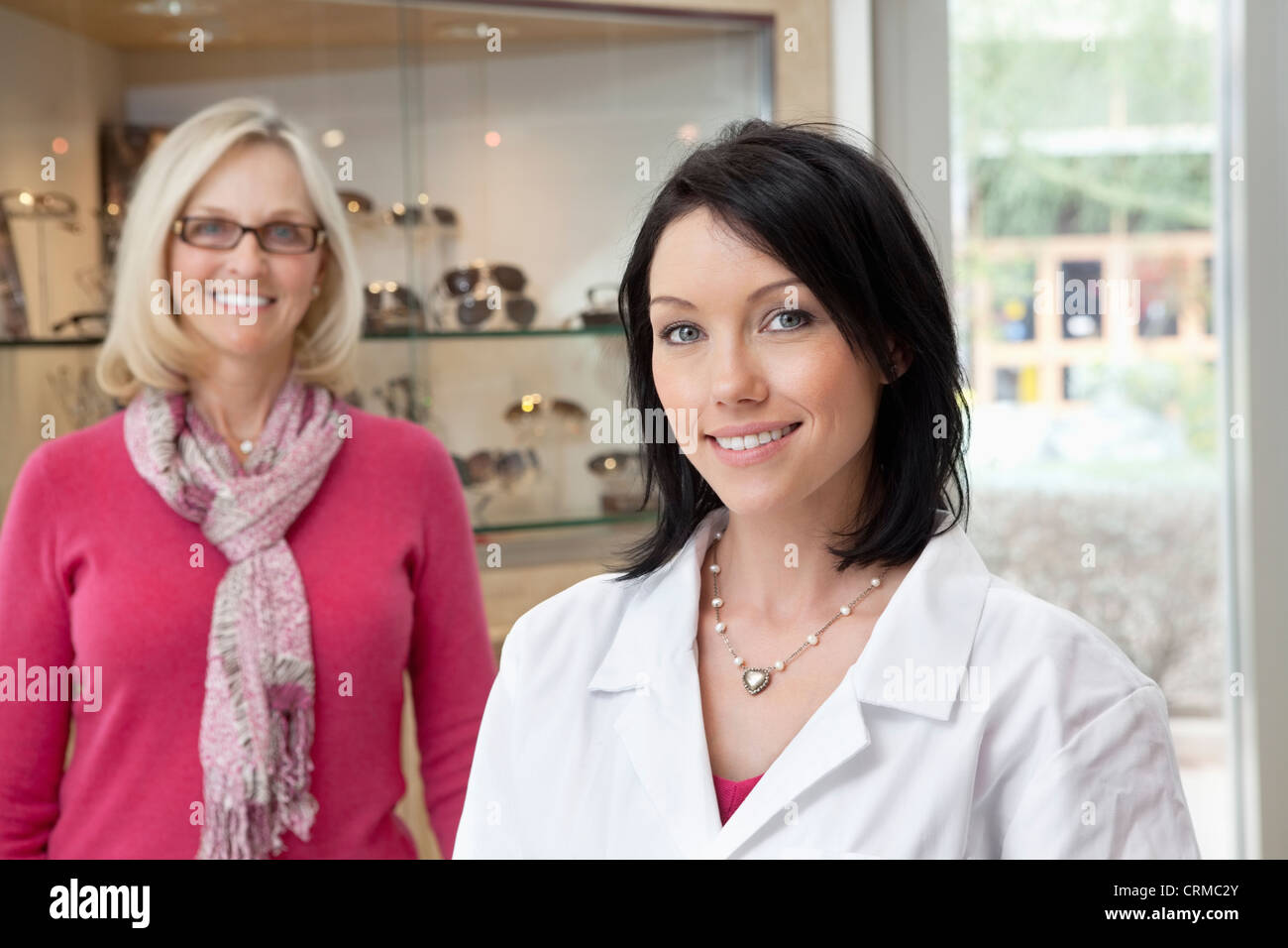 Portrait of a mid adult optometrist with female wearing glasses in background Stock Photo