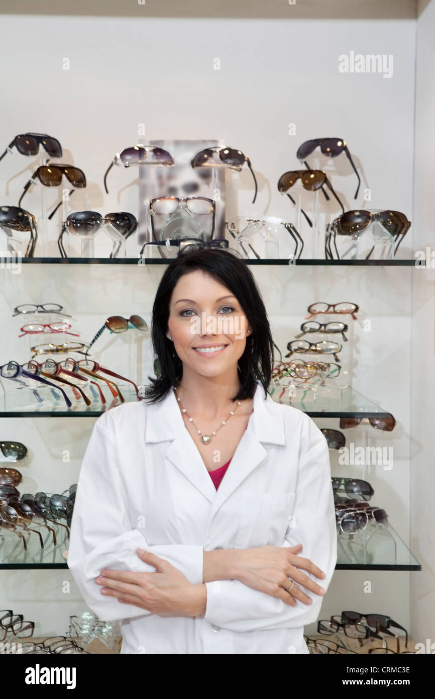 Portrait of a happy mid adult optician with arms crossed standing in store - Stock Image