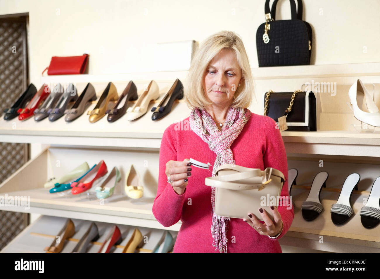 Mature woman looking at price tag of purse in store - Stock Image