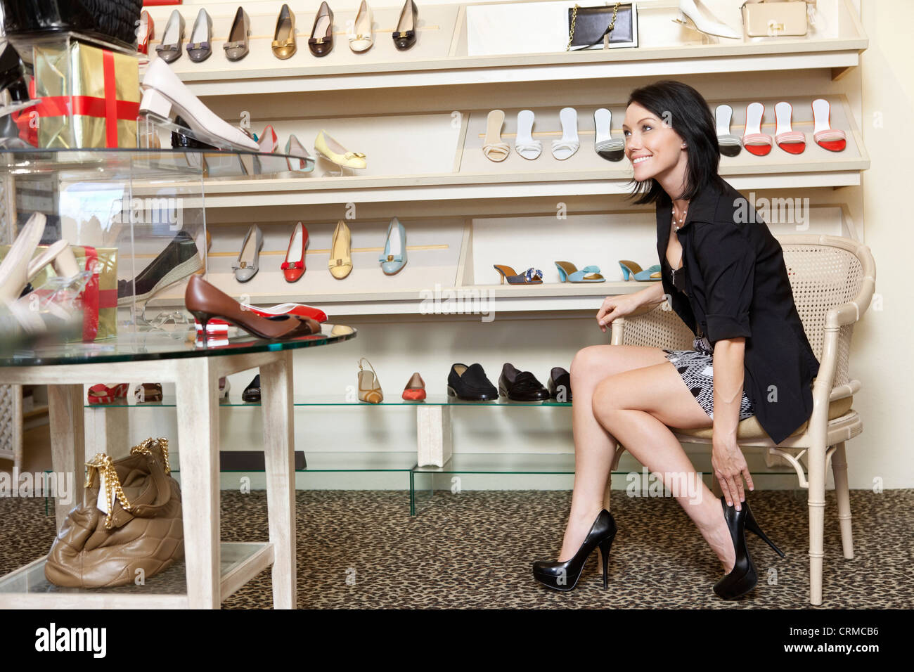 Happy mid adult woman trying high heels in footwear store - Stock Image