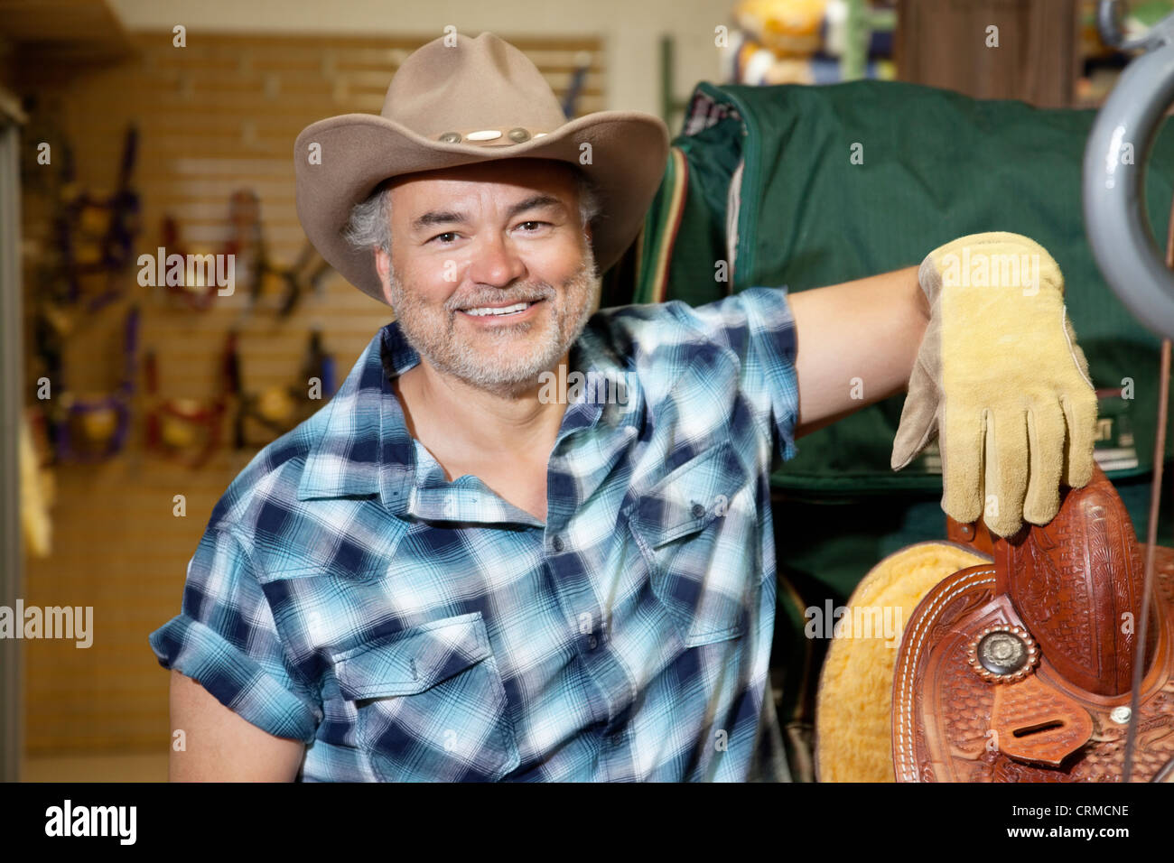 Portrait of a happy mature cowboy in feed store - Stock Image