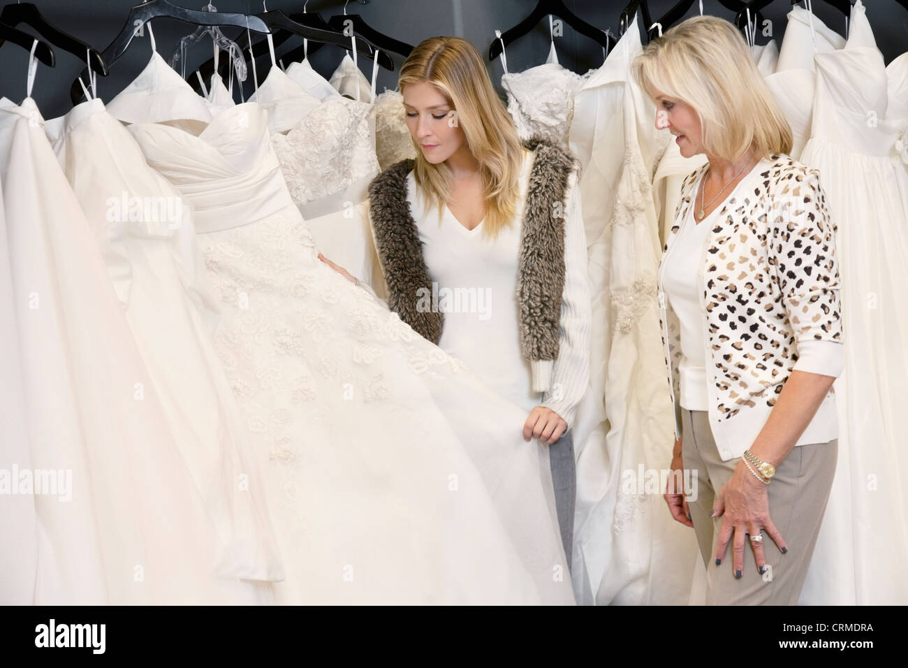 Young woman with senior mother selecting wedding dress in bridal store Stock Photo