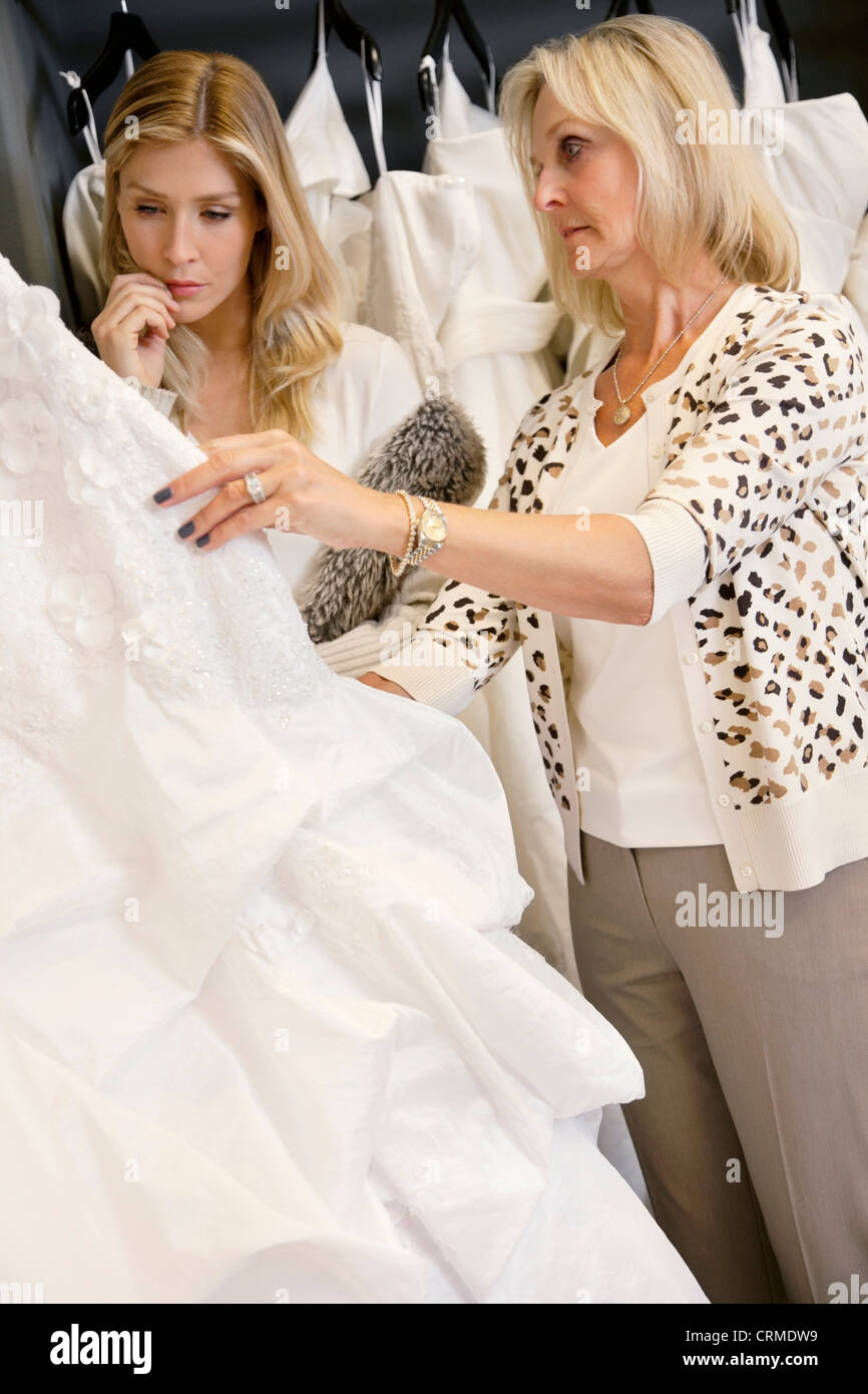 Mother selecting wedding dress for young daughter in bridal store Stock Photo